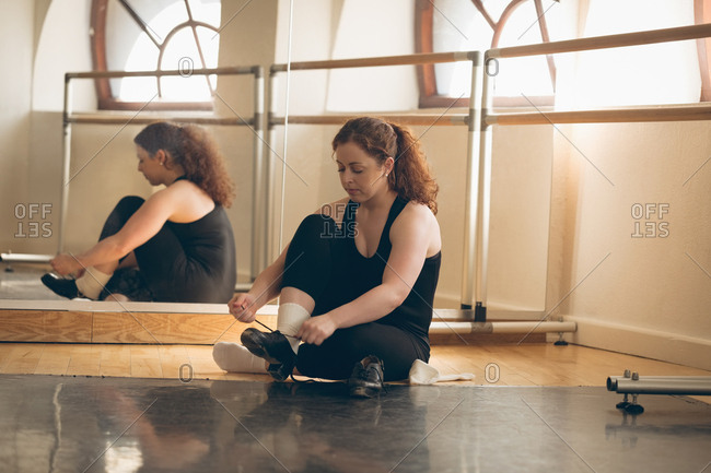 Irish dancer sitting on floor tying her shoelace in the studio