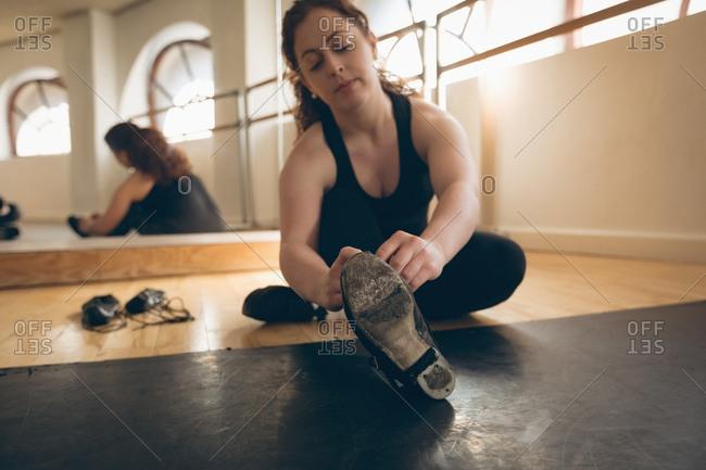Irish dancer sitting on floor tying her shoelace in the studio