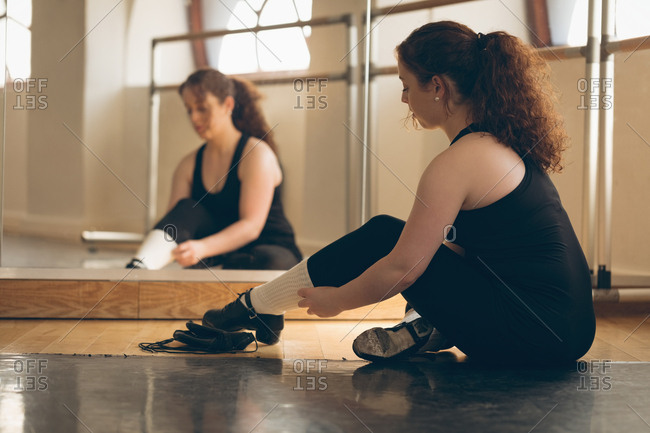 Irish dancer sitting front of mirror on floor tying her shoelace in the studio