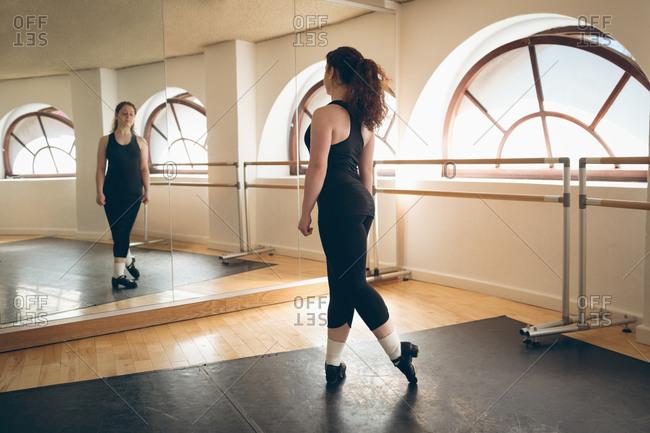 Irish dancer practicing in front of the mirror in the studio