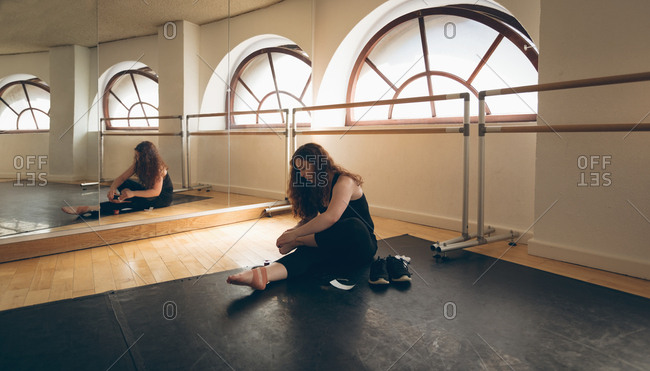 Irish dancer sitting front of mirror on floor in the studio