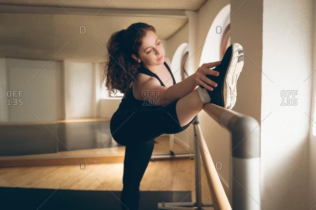Irish dancer performing stretching exercises in the studio