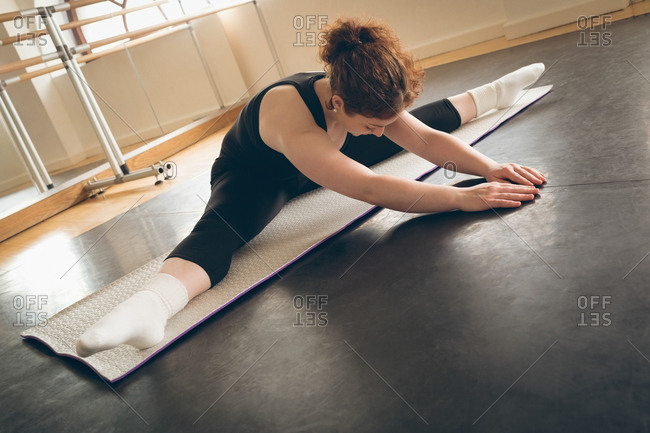 Irish dancer performing stretching exercises in the studio