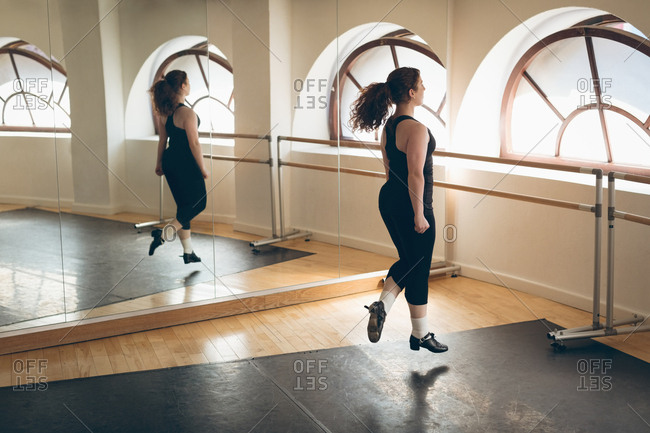 Irish dancer practicing in front of the mirror in the studio