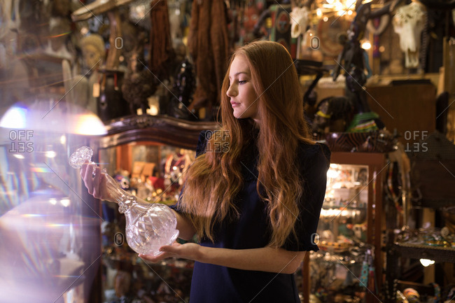 Woman selecting a glass vase in antique store