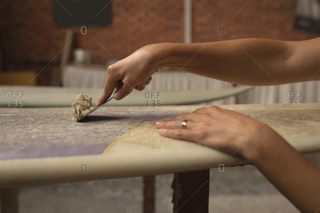 Female worker making surfboard in workshop