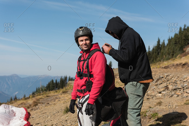 Man interacting with paraglider on mountain on a sunny day