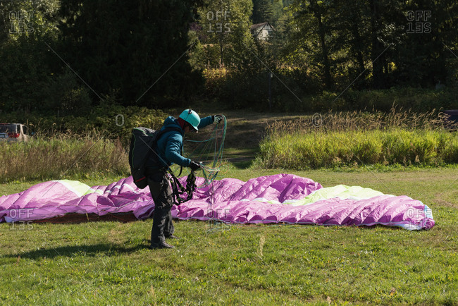 Paraglider landing on green landscape on a sunny day