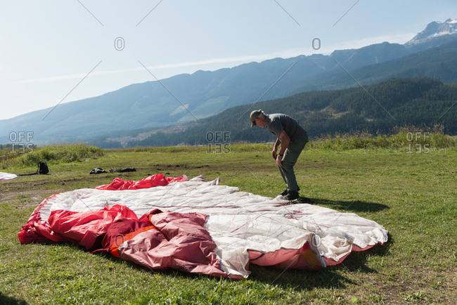 Paraglider preparing the parachute for paragliding on a sunny day
