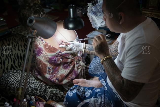 Chiang Mai, Thailand - November 16, 2017: European woman getting the Hah Taew Sak Yant Tattoo on her back