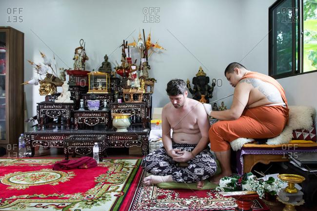 European man getting Sak Yant Tattoo on his back by a monk