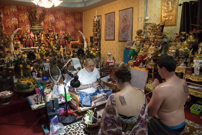 Chiang Mai, Thailand - November 16, 2017: European woman and man having a Sak Yant Tattoo Blessing by Sak Yant Master