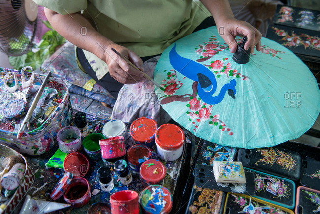 Person painting an umbrella made of mulberry paper