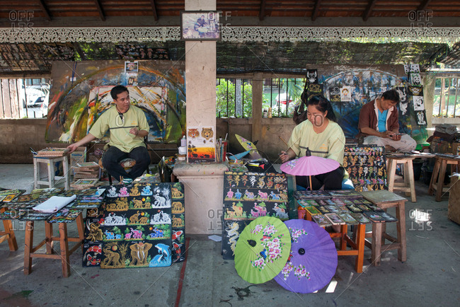 Chiang Mai, Thailand - November 24, 2017: Thai painter painting on an umbrella made of mulberry paper