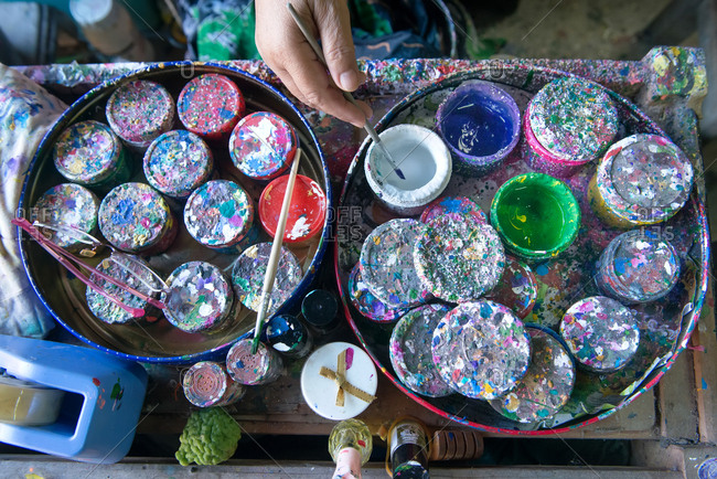 Chiang Mai, Thailand - November 24, 2017: Multiple color containers, a brush mixing color