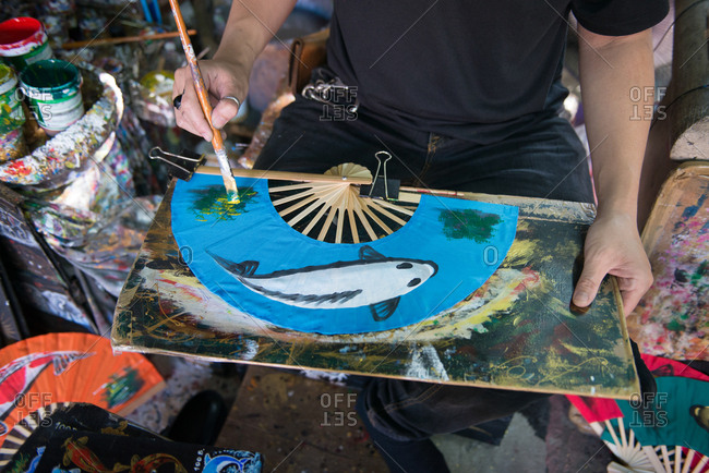 Man painting carp fish on a folding fan