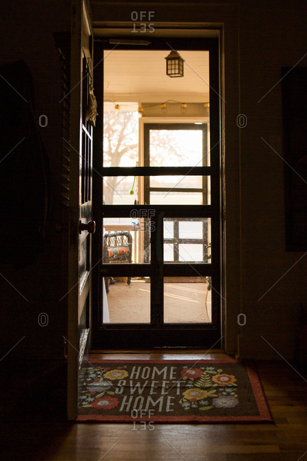 Front door open to porch with home sweet home doormat