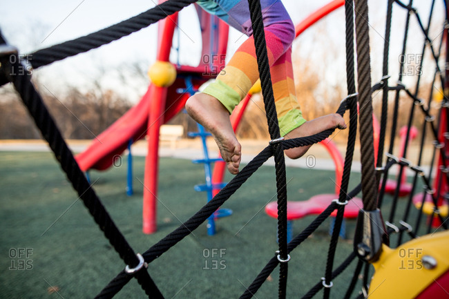 Child with dirty feet climbing rope structure at playground