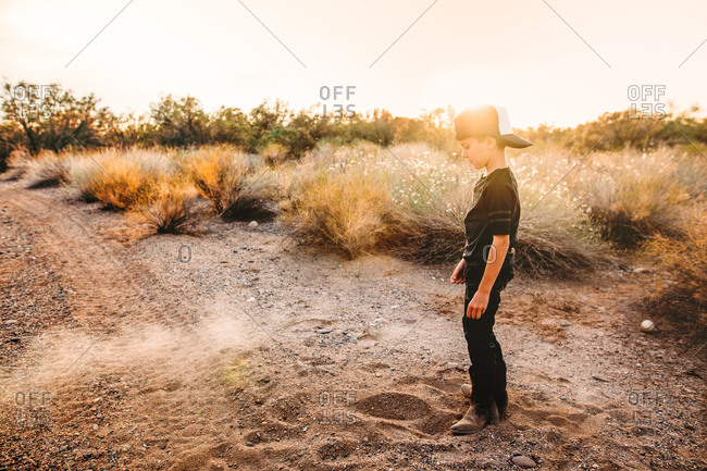 Boy standing in desert sand at sunset
