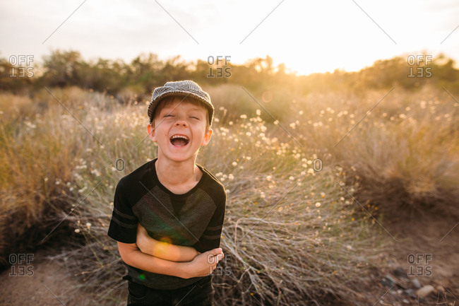 Little boy standing by desert plant laughing