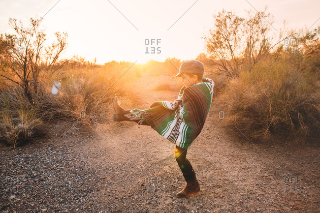 Boy kicking a can in the desert at sunset