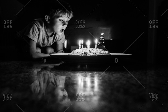 Boy blowing out birthday candles in black and white