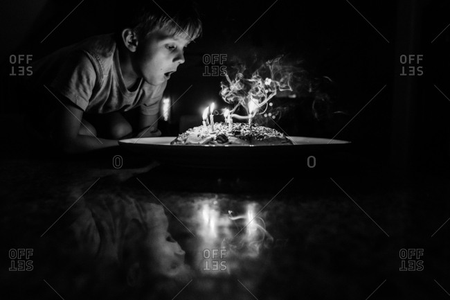 Smoke from boy blowing out birthday candles in black and white