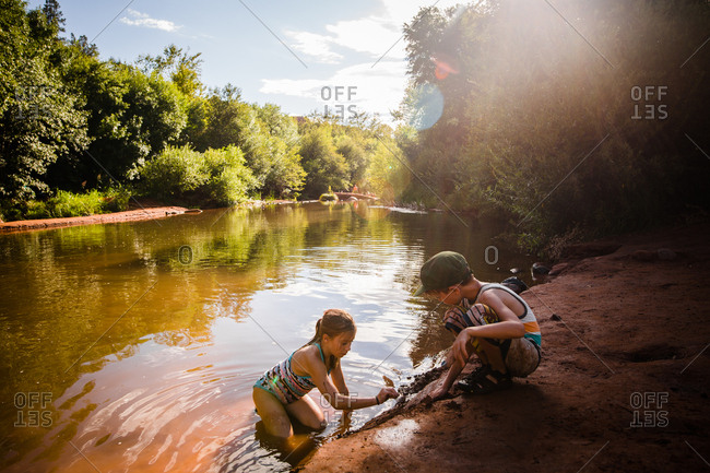 Kids playing on a riverbank