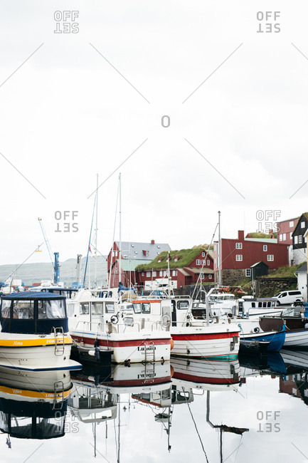 Torshavn, Faroe Islands - August 4, 2017: Boats reflected in the calm waters of harbor