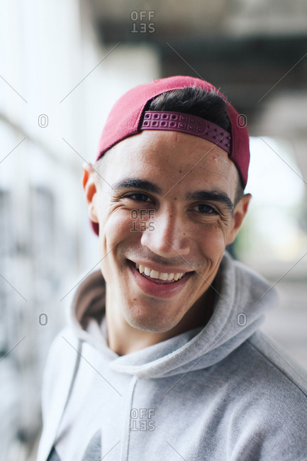 Portrait of trendy young man smiling in athletic wear and a backward baseball cap