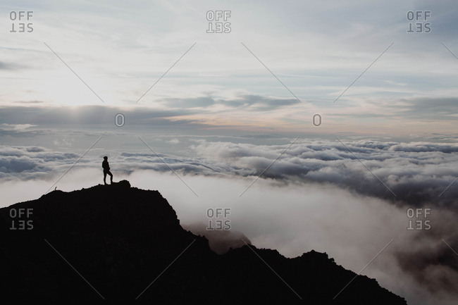 Silhouette of a hiker at sunrise above the clouds on the top of the Mount Rinjani