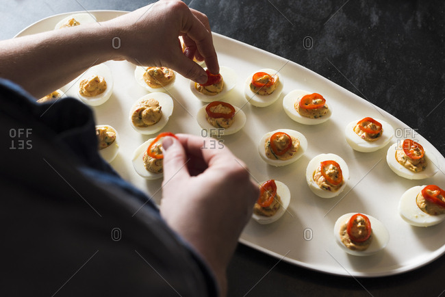 Person preparing a platter of deviled eggs