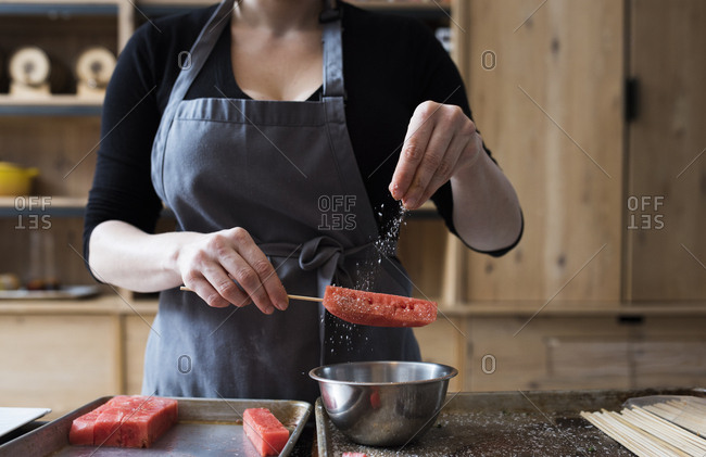 Person salting a watermelon stick