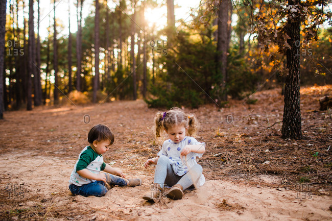 Two small children sitting in a forest playing in sand
