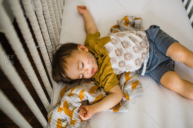 Toddler boy asleep in crib with arms spread