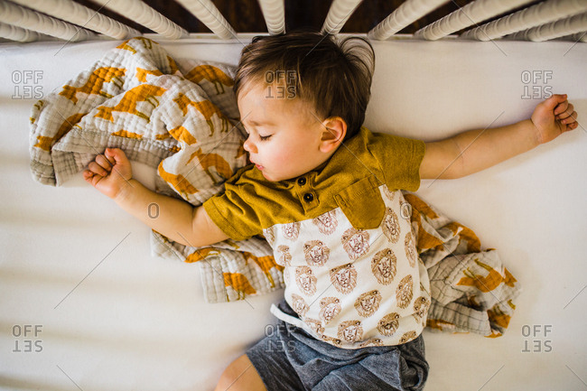 Overhead view of toddler boy asleep in crib with arms spread