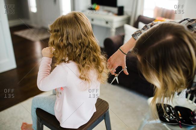 Woman giving toddler girl a haircut at home