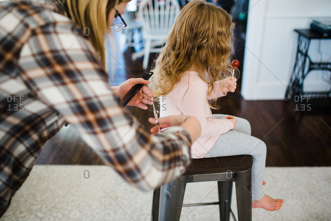 Woman giving little girl a haircut at home