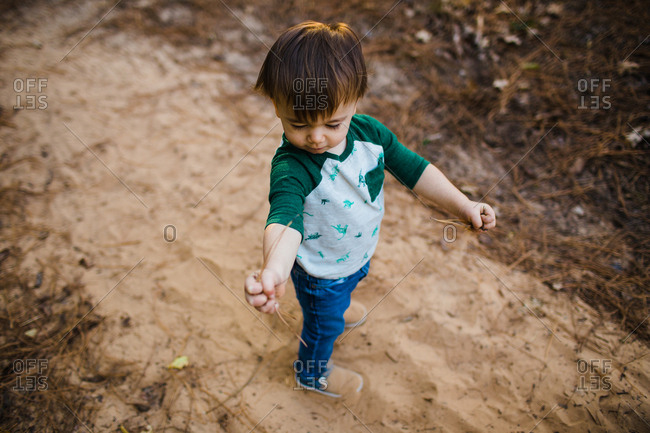 Toddler boy playing in sand in the woods