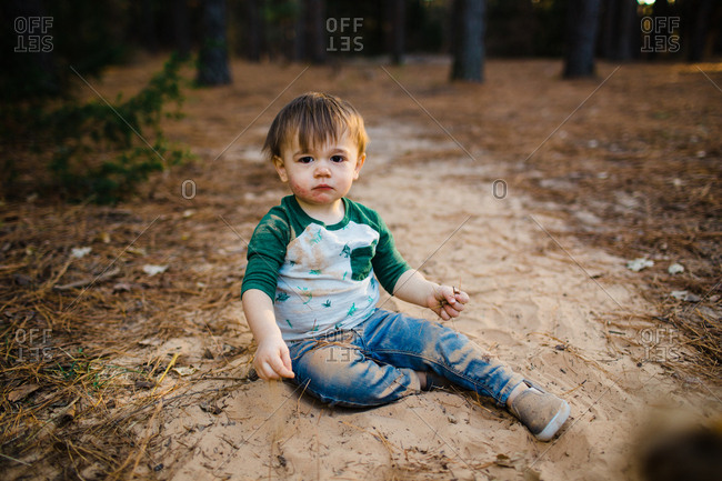Toddler boy sitting and playing in sand in the woods