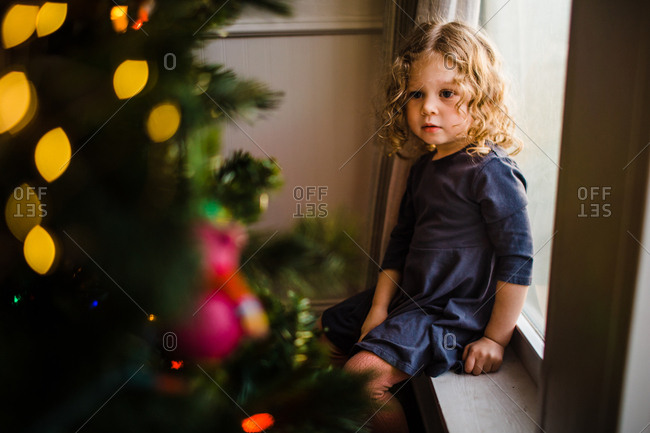 Girl sitting on windowsill looking at a Christmas tree