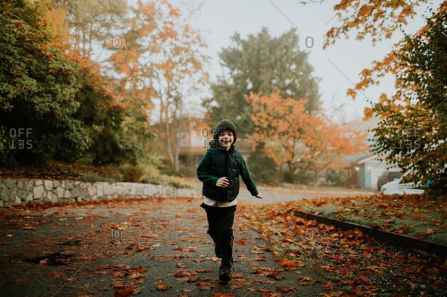 Boy running on leaf covered driveway