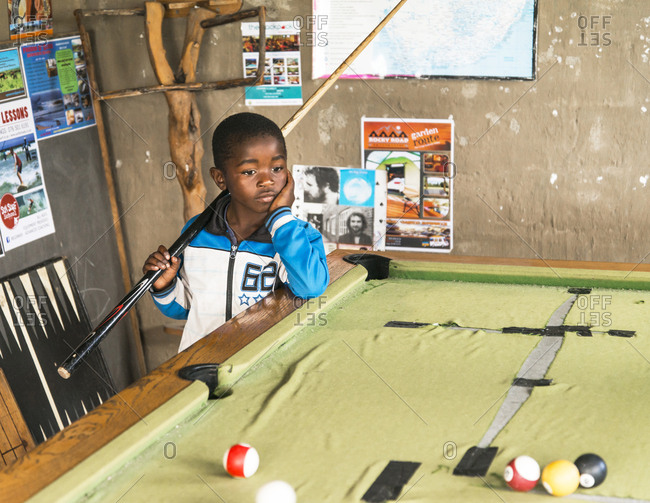 Mdumbi, Eastern Cape South Africa - September 8, 2017: A portrait of a young South African boy looking thoughtful as he contemplates his next shot while playing a game of pool