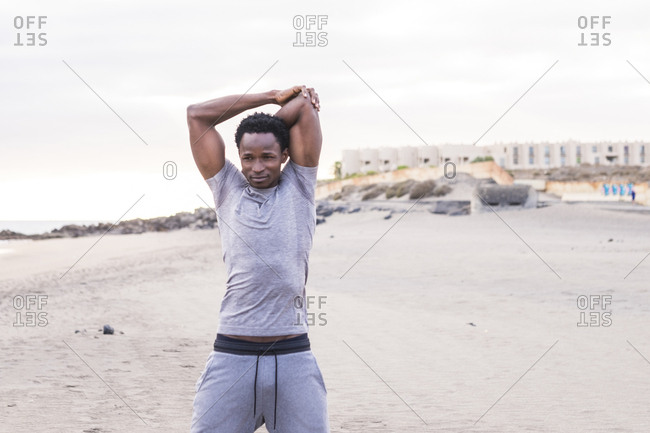 Young man stretching arms before a workout on the beach