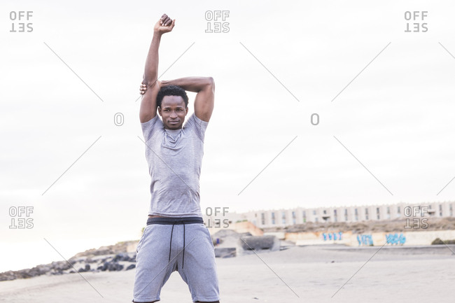 Young man stretching his arm before a workout on the beach