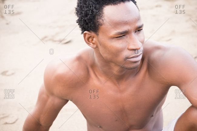 Close up of an athletic man resting on a beach
