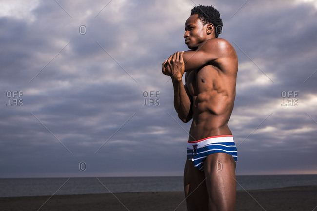 Profile view of man stretching arms in swimwear before beach workout
