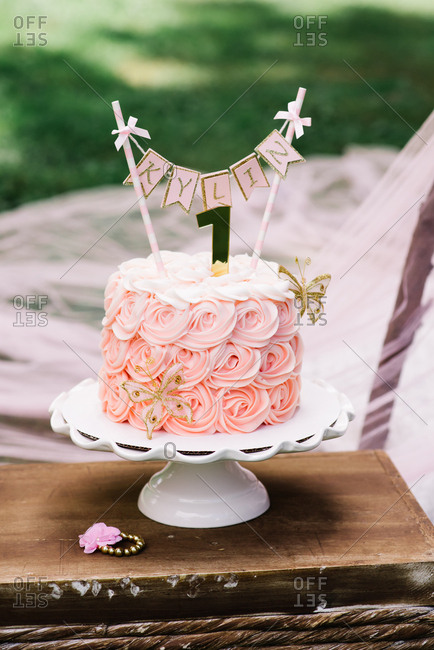 Pink birthday cake celebrating baby's first birthday served on cake stand