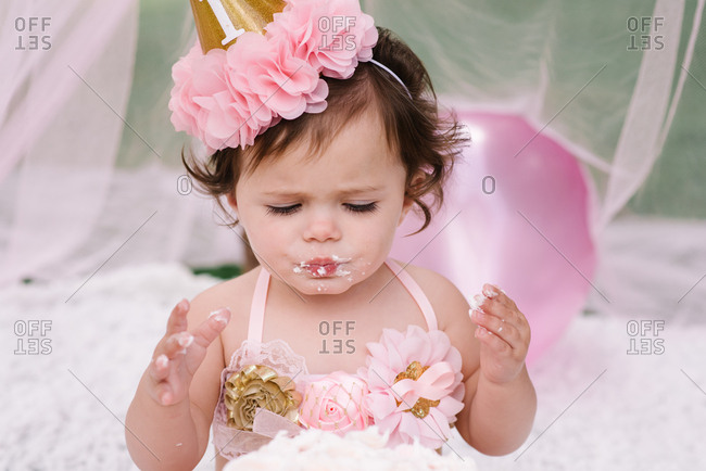 Baby with cake on her face at first birthday party
