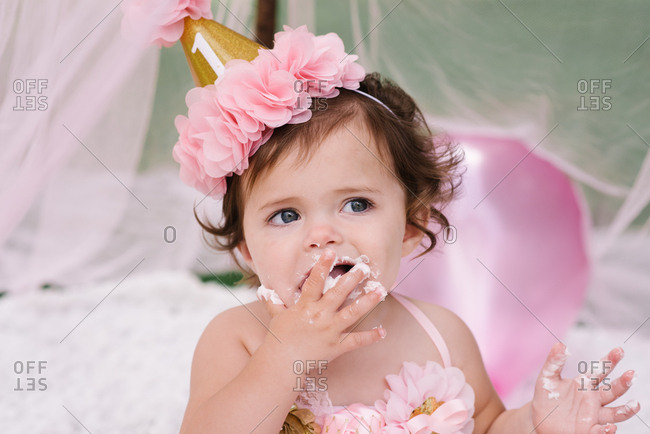 Baby girl licking frosting off her fingers at first birthday party